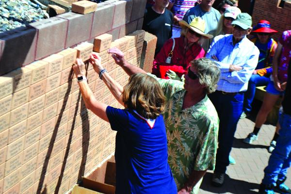 Jenny Johnerson places a memorial brick for her father, WWII veteran Alfred Thorwaldson, on the Ennis veterans' memorial wall at the commemoration ceremony on July 4. Twenty-three new commemorative bricks were places on the wall at the ceremony.