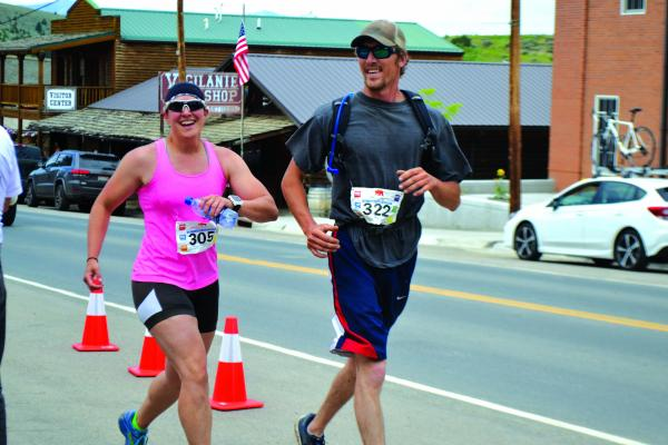 Carrie Egging and Tyler Behm of West Yellowstone grin as they cross the finish line of the Madison Duathlon on Sunday, July 8. The pair finished in just under 3 hours, 45 minutes, biking 14 miles and running 7 miles to travel from Ennis to Virginia City.