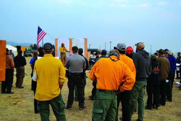 Fire crews and personnel listen to Jeff Winger discuss the day's fire suppression strategies at an early-morning briefing on Friday, August 17. The Monument and Wigwam fires saw little change toward the end of last week. (R. Colyer)