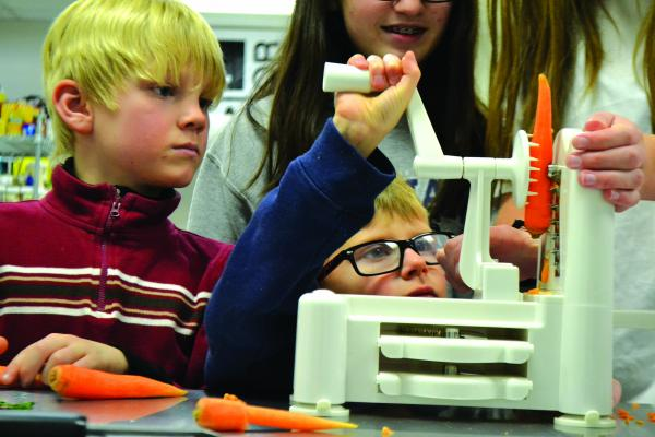 Some of the first-grade students learning about preparing and cooking local carrots used a spiralizer for the first time on Monday, December 10. It took a little bit of elbow grease, so help from some high school students was appreciated. (R. Colyer)
