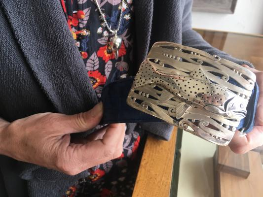 Black Jack Ranch Gallery opening director and featured artist Ellie Thompson holds one of her handmade sterling silver belt buckles, featuring a cutthroat trout. Her buckles feature materials found in Montana, like sterling silver and Montana sapphires. (Reagan Colyer photo)