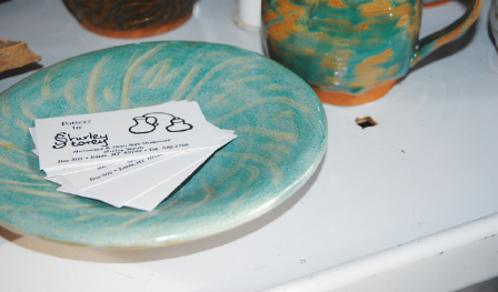 Masson's business card laying on one of her earth-toned pottery pieces. She displays finished items in a sunny room in her basement. PHOTO by Keeley Larson