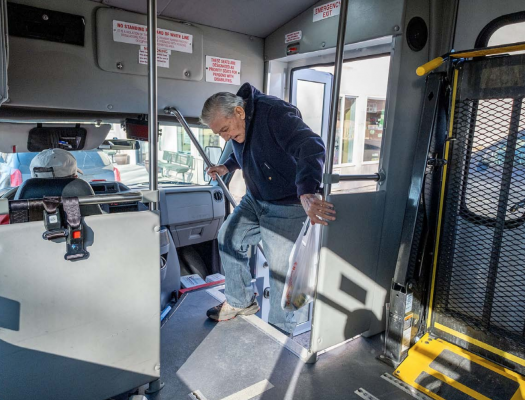 After shopping at The Corner Store, Whitehall resident Bruce Ball boards a Whitehall Public Transportation bus driven by LeRoy Murphy Feb. 21, 2020. (Ball has since passed away.) PHOTO BY JOHN BLODGETT, BOULDER MONITOR