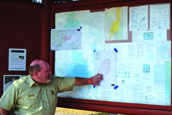 Above - Beaverhead-Deerlodge National Forest District Ranger Dave Sabo briefs visitors on the status of the Monument and Wigwam fires at the Ennis Forest Service office on Monday, August 13. (R. Colyer photo).