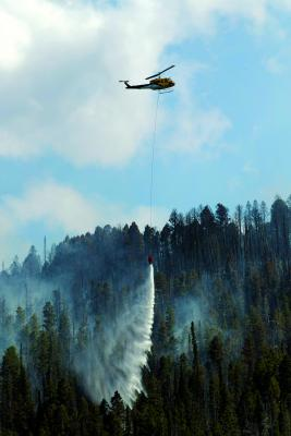 A helicopter drops water on the Virginia Creek fire to help get it under control. The fire burned 15 acres as of Friday, Aug. 3, and threatened private property and homes in the South Meadow Creek area. (Howard Sheridan photo)