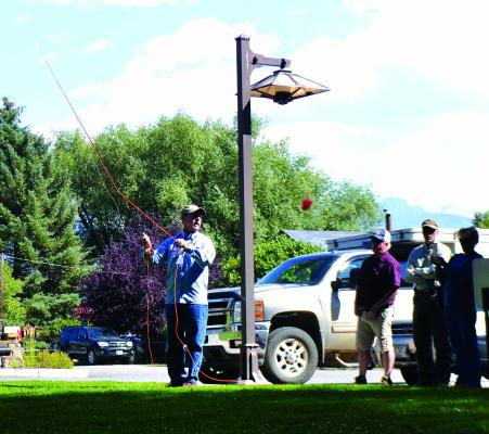 Attendees of the Fly Fishing and Outdoor Festival take part in a casting clinic on Friday, August 31. The festival drew hundreds of visitors from around the west. The red blob near the pick-up is the fly, and the fly caster was accurate, he nearly hit the photographer's camera. (R. Colyer)