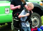 USFS Madison Ranger District fire crew member Sarah Rife, helps Sheridan third grader David Reeves try on a typical wildfire fighter's field backpack at Bear Creek Days Tuesday, May 14. (H. Kearse)